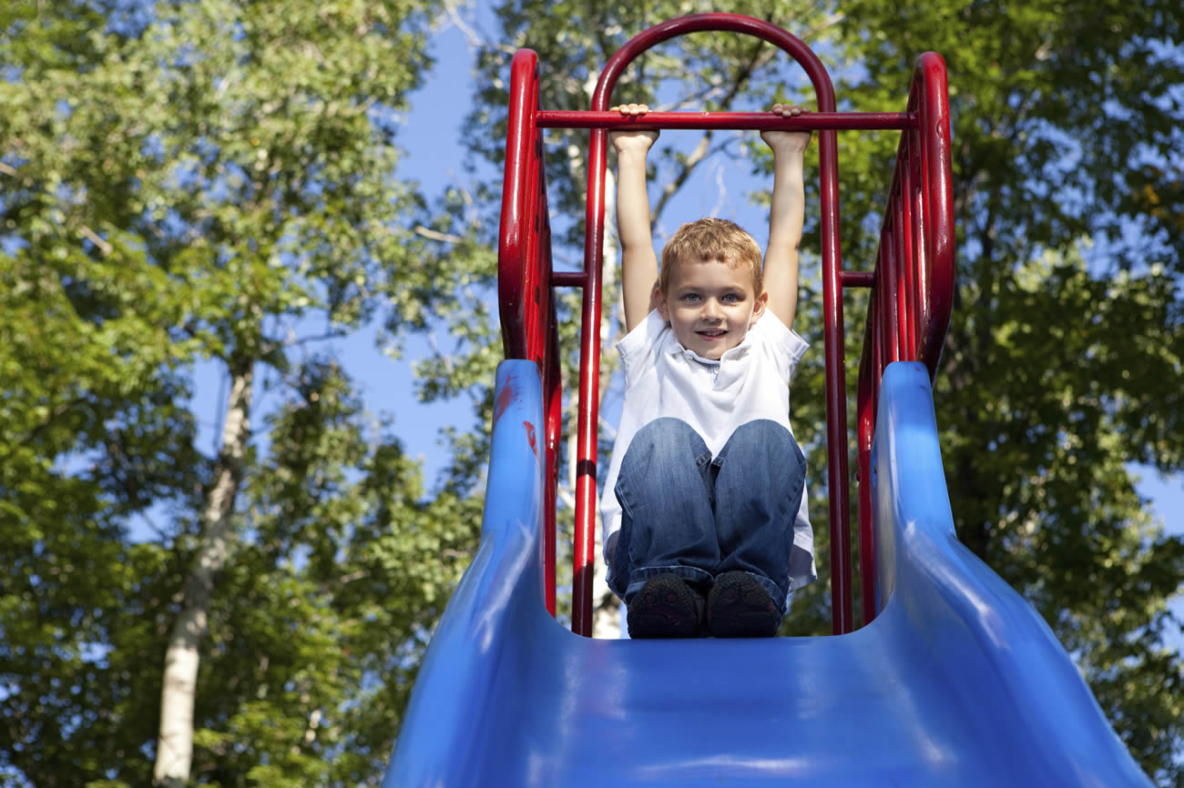 Boy-Playing-on-a-slide-at-the-park–Stock-Photo-playing-children-playground