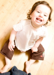 Happy toddler sitting on floor with others